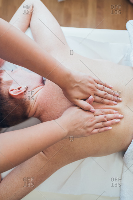 Masseuse indoors doing back massage on a customer - pampering, comfortable, relaxing concept