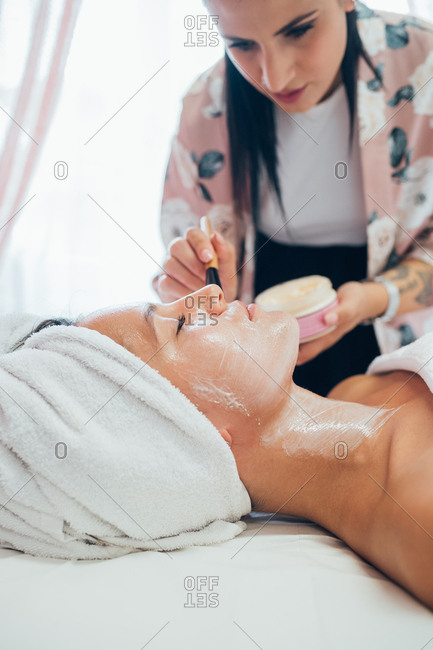 Beautician applying face mask on a customer - relaxation, spa treatment, health and beauty concept