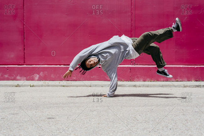 Young hispanic men doing acrobatics near to a pink wall on the street