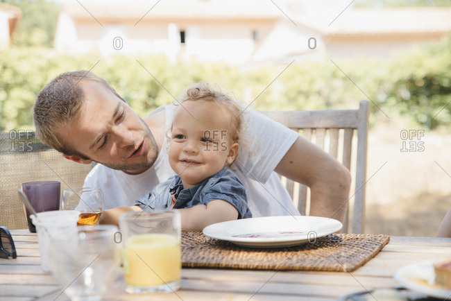 Father with son on lap at outdoor table