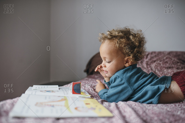 Toddler laying on the bed looking at a picture book