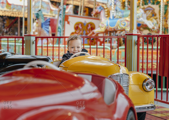 Little boy excited to be on car ride at amusement park