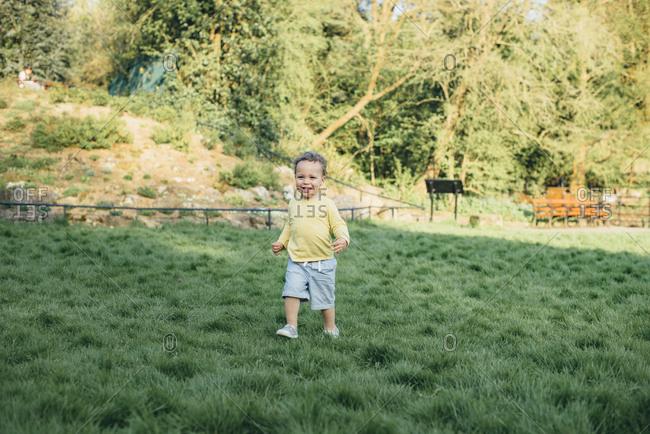 Boy walks on grass in park