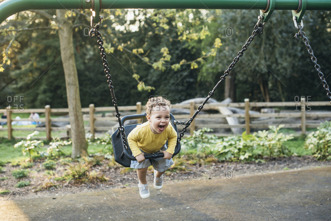 Silly boy screaming on a swing