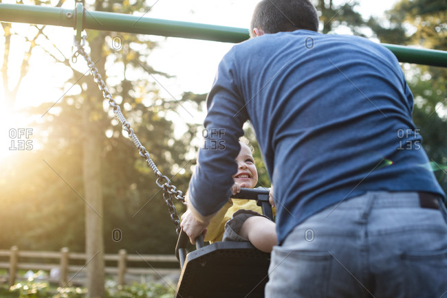 Boy with his father on swing