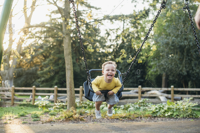 Smiling kid on swing in playground
