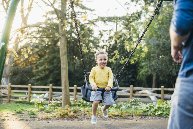 Toddler boy smiling on swing looking at dad