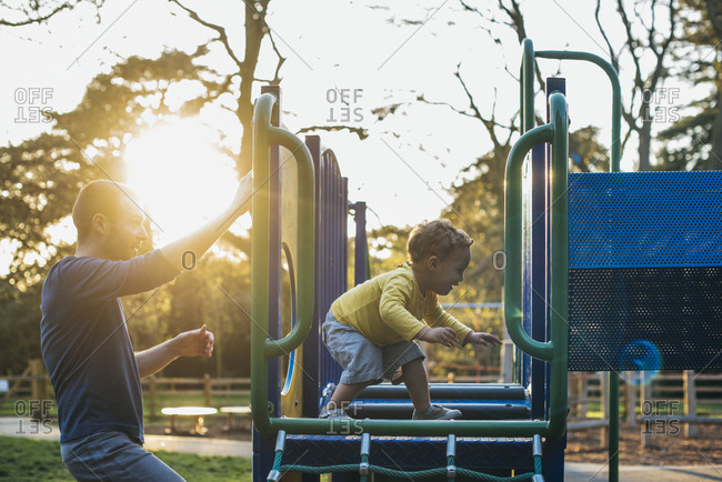 Father and son play on playground equipment