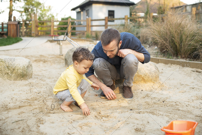 Father and son play with sand in sandpit