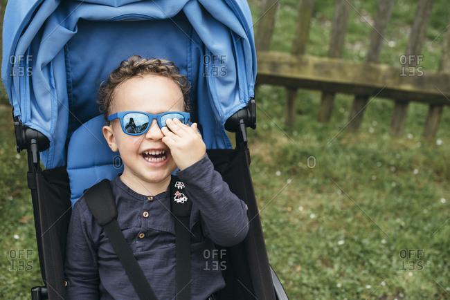 Boy wearing glasses sits in stroller