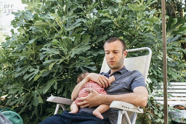 Father holding his sleeping newborn son