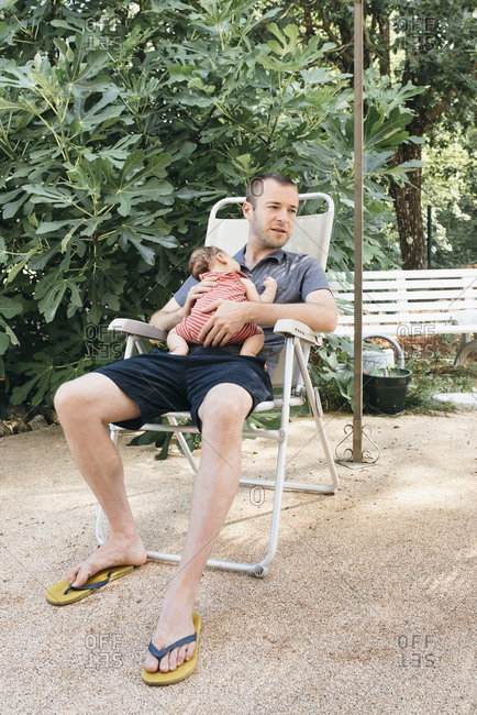 Father holding his newborn son while sitting outside