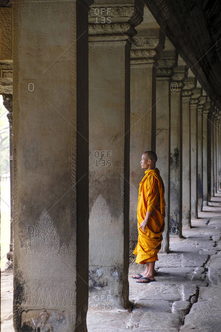 January 12, 2016: Buddhist monk in a colonnaded corridor in a temple in Angkor Wat, UNESCO World Heritage Site, Siem Reap, Cambodia, Indochina, Southeast Asia, Asia