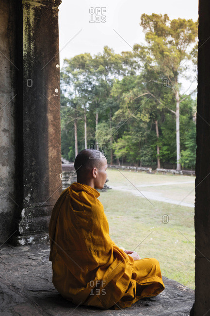 January 12, 2016: Buddhist monk sitting in a colonnaded corridor in a temple in Angkor Wat, UNESCO World Heritage Site, Siem Reap, Cambodia, Indochina, Southeast Asia, Asia