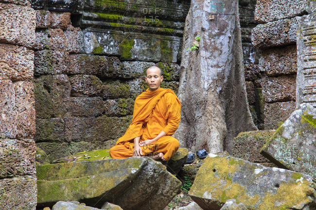 March 21, 2018: Buddhist monk sitting in a ruined temple in Angkor, UNESCO World Heritage Site, Siem Reap, Cambodia, Indochina, Southeast Asia, Asia