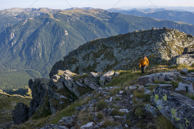 August 25, 2017: A hiker climbs along a high ridge near Maliovitsa in the Rila Mountains with distant views of valleys and hills, Bulgaria, Europe