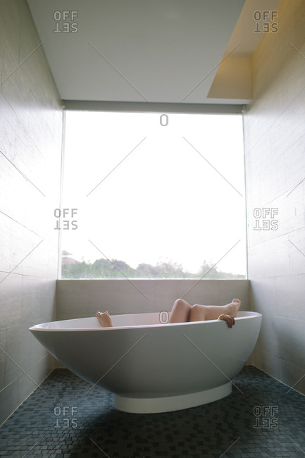 A womans hands and legs poke out of a white bathtub as she relaxes