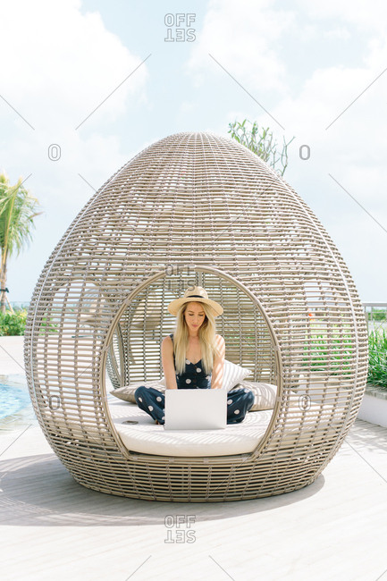 A blonde woman wearing a hat works remotely on her laptop from a trendy outdoor lounge