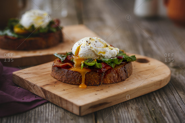 Open sandwich with poached egg with runny yolk and collard greens
