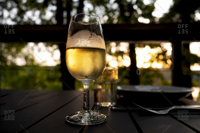 Glass of white wine served on outdoor patio at sunset