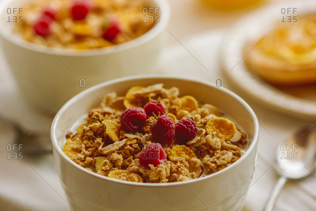Bowl of vanilla almond clusters cereal topped with fresh raspberries