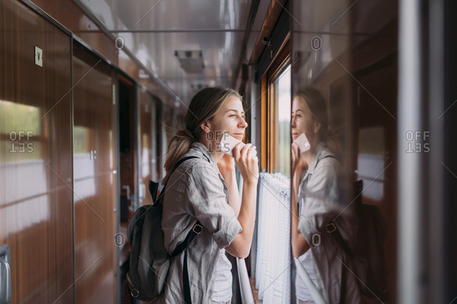 Young woman on train holding smartphone and looking out window