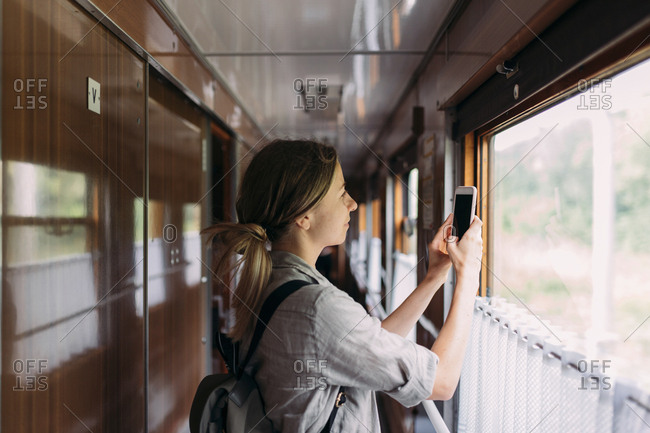 Young woman using her phone to take a picture outside of train window