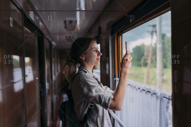 Young woman taking a picture with her phone outside of train window