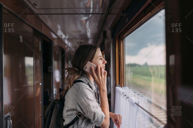 Young woman talking on phone while looking at the scenery out of train window