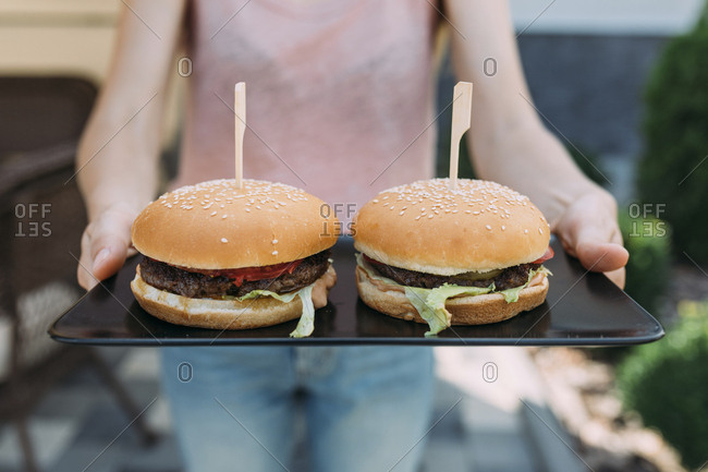 Person serving two hamburgers on tray