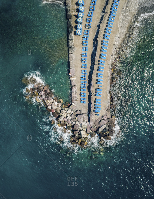 Aerial scenic view of rocky and sandy small peninsula with bright blue parasols and beach chairs surrounded by beautiful ocean