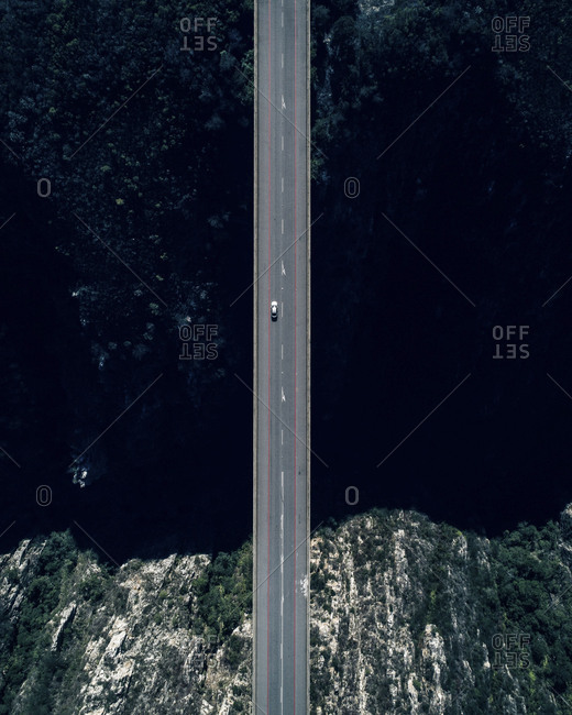 Aerial view of small car driving on empty road of bridge across dark ocean bay water with rocky coastline