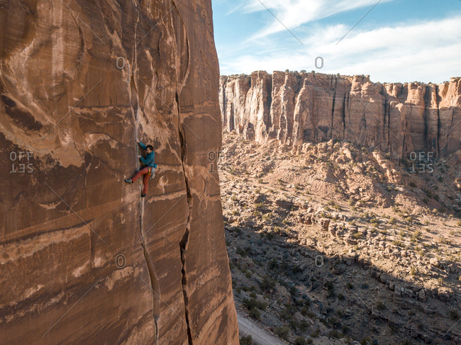 Moab, Utah, United States - November 3, 2017: A climber ascends a sandstone crack high above the valley floor.