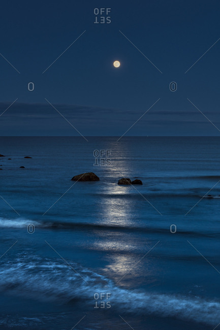 The rising full moon reflecting on the ocean at dusk with waves breaking into the shore.