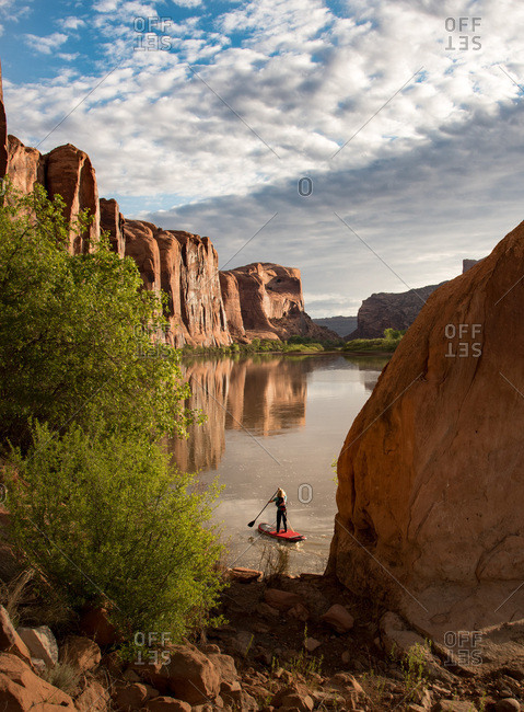 A woman navigating on a stand up paddle board on the Colorado River.