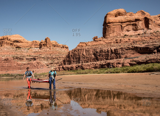 Moab, Utah, Usa - April 21, 2018: A woman and a man carrying their stand up paddle boards along the Colorado River.