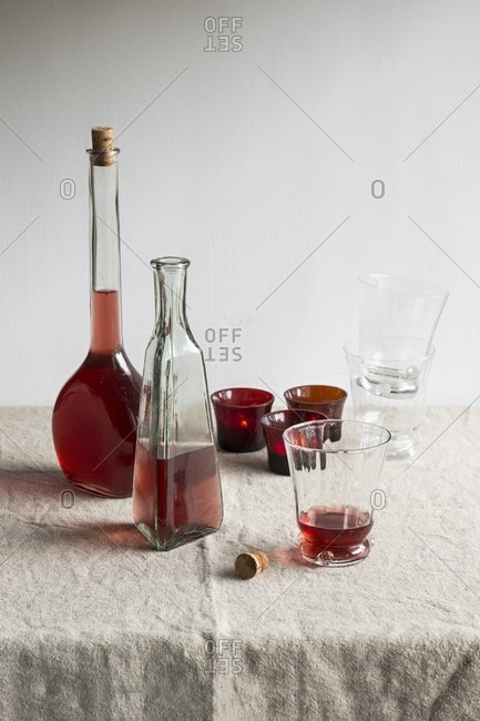 Rose wine in bottles and a glass on a beige tablecloth