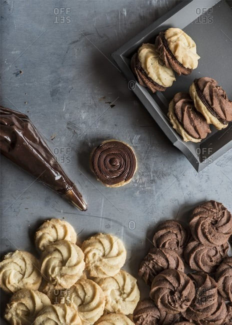 Viennese swirl cookies filled with chocolate cream, on a metal background