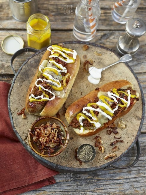 Chilli hot dogs topped with fried onion, mustard and mayonnaise