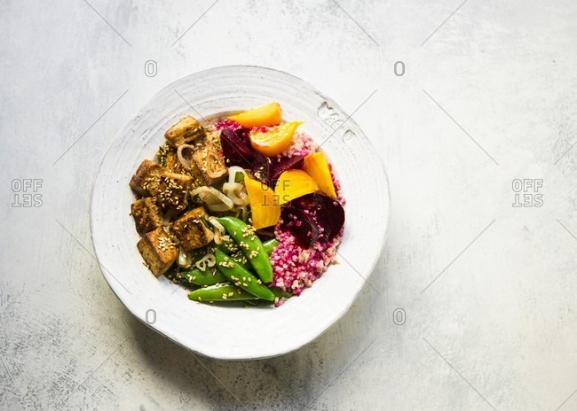 Pickled golden and red beets tossed with quinoa, topped with grilled tofu and sugar snap peas