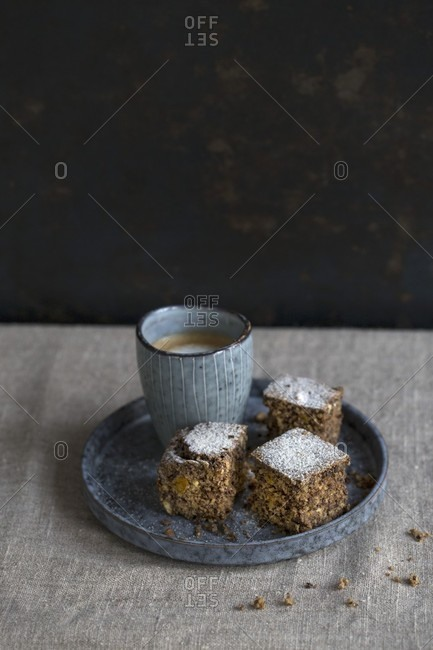 A brownie with small cup of cappuccino on a linen blanket