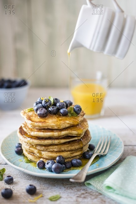 Stack of pancakes with lemon zest, blueberries and maple syrup for breakfast