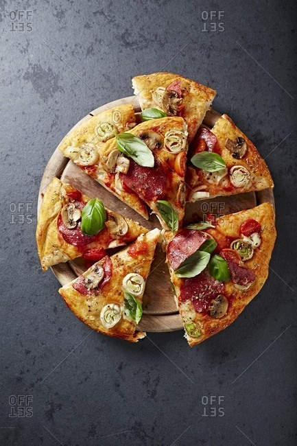Pizza with mushrooms, salami and leek on a chopping board