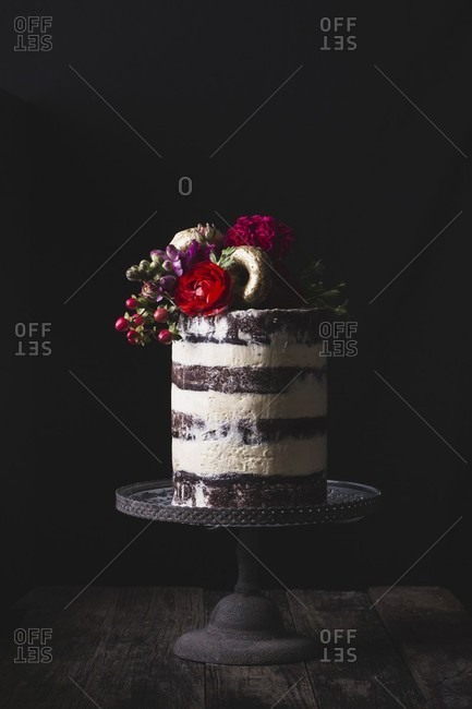 Layered wedding cake on stand decorated with fresh flowers and gold donuts