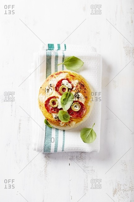 Mini pizza with green olives and salami