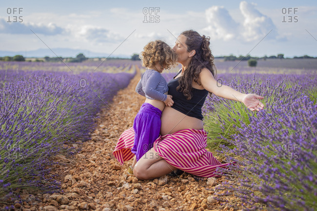 Side view of happy pregnant woman kissing little daughter while sitting on pathway in blooming lavender field