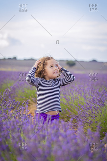Little curly innocent girl sanding in blooming lavender flowers and looking up in dreams