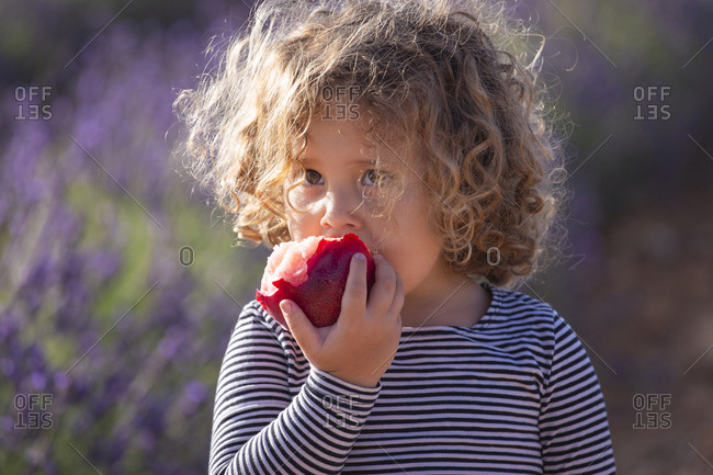 Adorable little girl with peach in sunlight