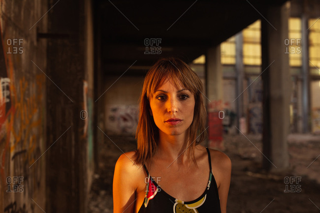 Serious adult woman in dress standing in sunset light on grungy background of concrete abandoned interior