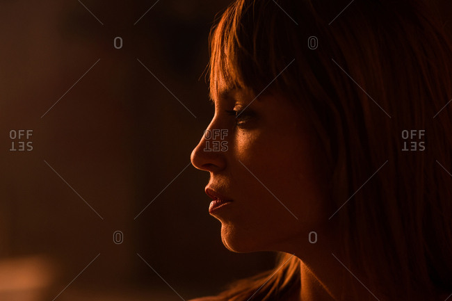 Close-up of emotionless young woman with bangs standing in soft gold light of sunset looking away